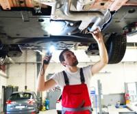 Mechaniker in einer Werkstatt kontrolliert den Unterboden eines Autos // mechanic in garage checked car